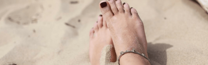 persons feet in sand